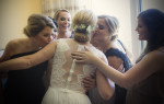 Emma is embraced by her bridesmaids after putting on her dress.