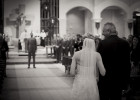 A bride walks down church aisle with her father.