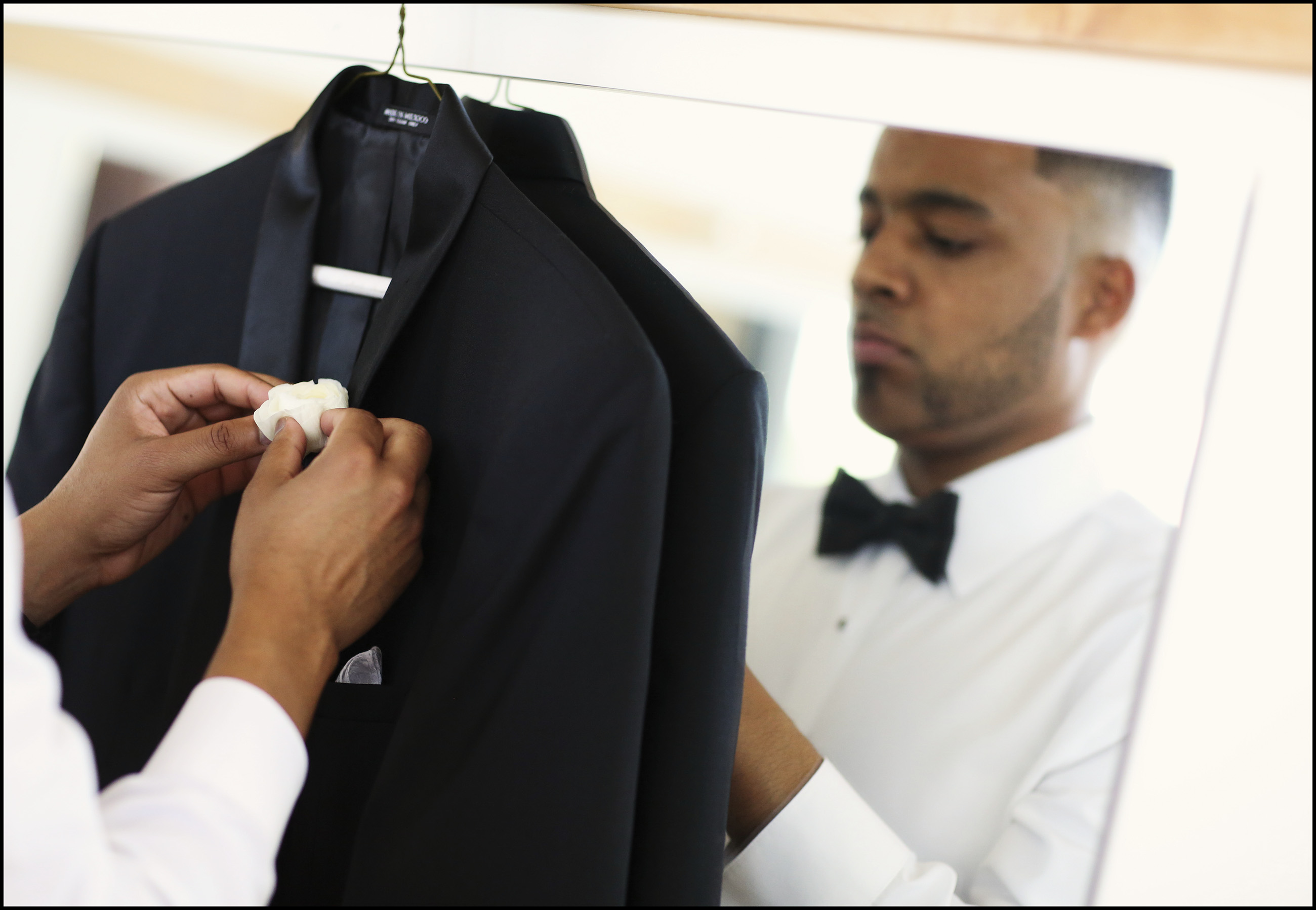A groom puts himself together before his wedding.