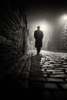black and white. A man in a hat and coat walks down a cobbled street on a foggy night.