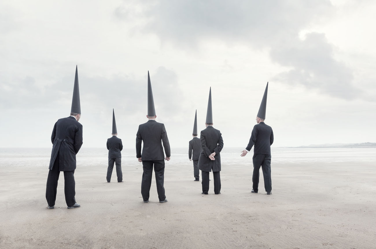 six Conemen in black suits stand on an empty beachwith their back to the viewer