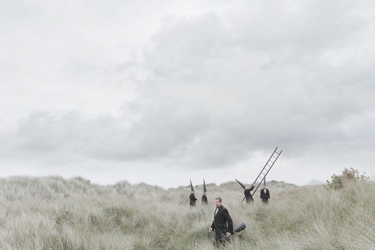 Conemen standing in a grassland landscape with a ladder.