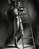 vintage style black and white nude woman solarised image in surreal style behind a ladder