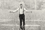 a man stands in a lake like a preacher, his arms held out, while water runs through his hands as if in baptism