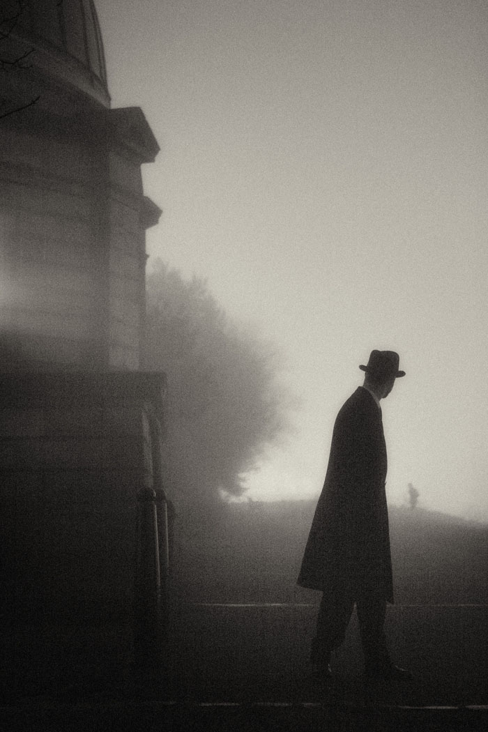 man in long coat and bowler hat looks down a road into the mist at night