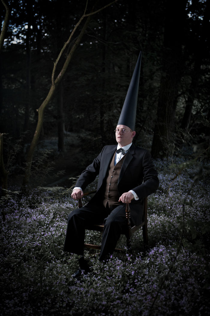 a Coneman sits in a grand wooden chair in the middle of a wood at night with flowers all around him.