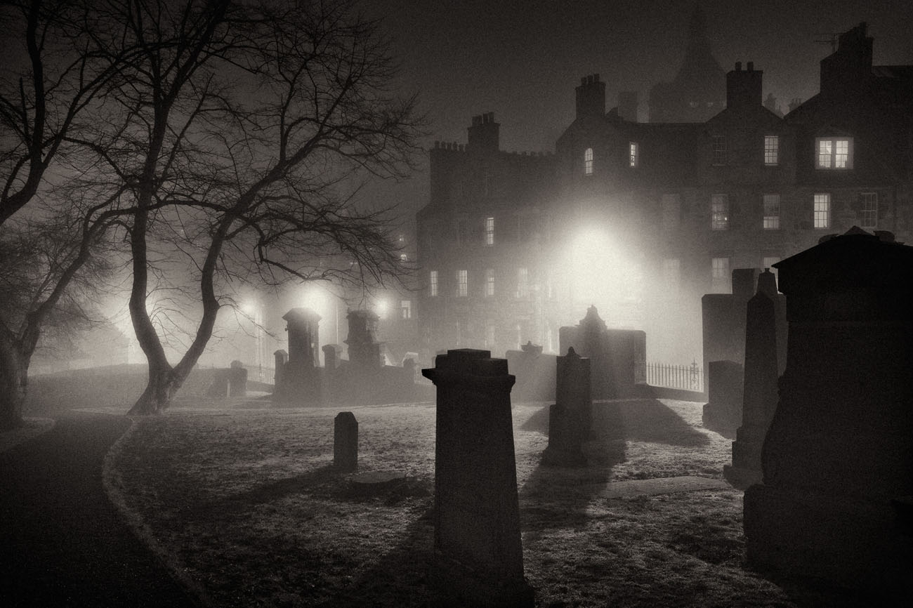 light filtering through the fog onto gravestones in Greyfriars Kirk at night