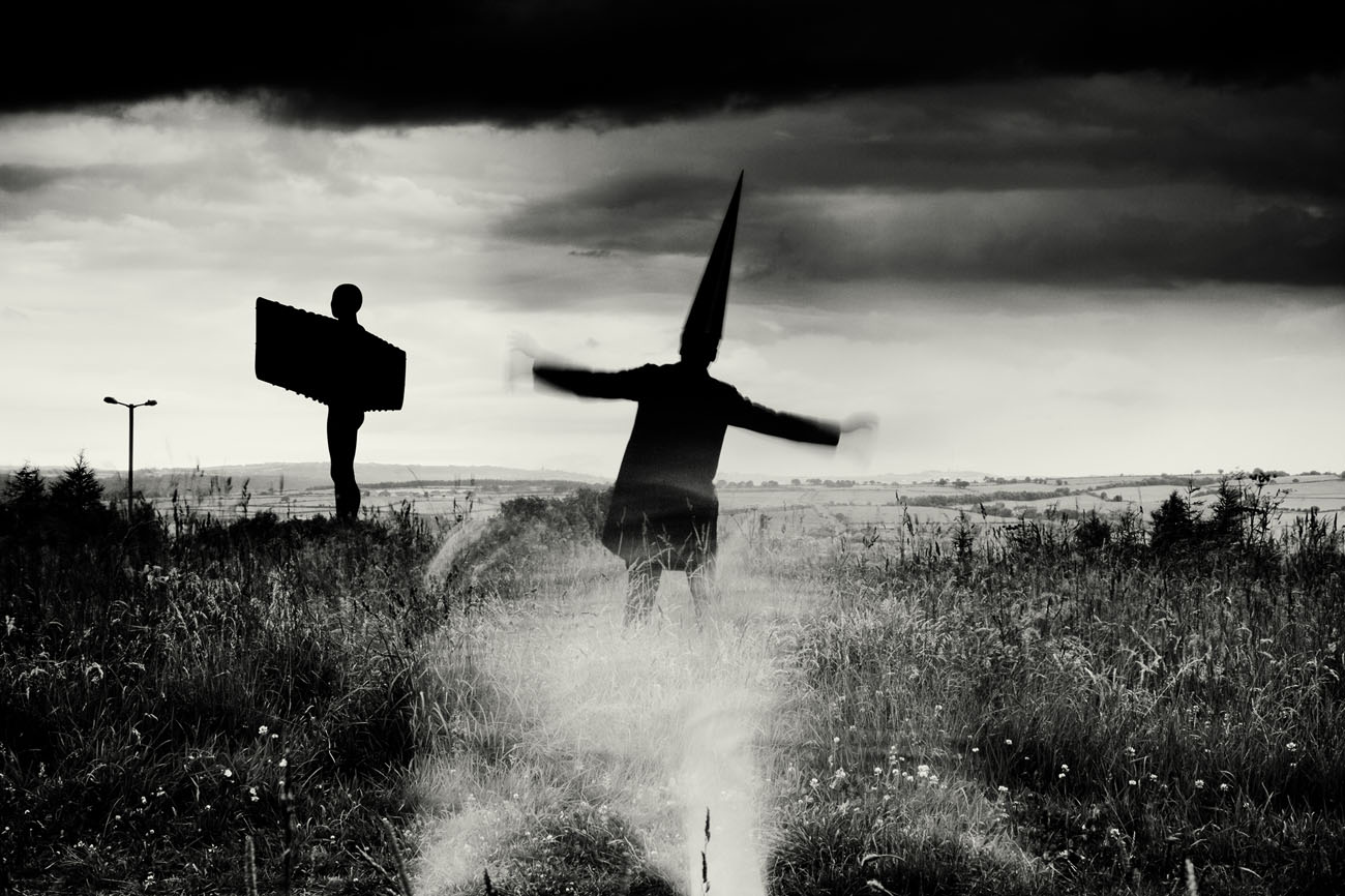 a Coneman stands before the Angel of the North flapping his arms . Black and white landscape photograph with a moody sky.