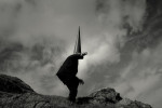 a lone Coneman leaps off a stone in a country landscape. Black and white fine art photo