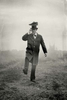 vintage image of a man walking with a shoe on his head.