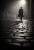 lone man walks down a cobbled steet in the fog at night