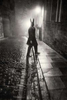 a man in a hare mask on a wet cobbled street at night