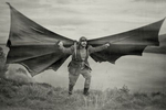a man playing otto lilienthal with giant wings about to take off