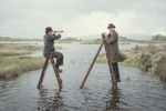 surreal Photograph of two men sitting on ladders in rannoch moor loch in Scotland