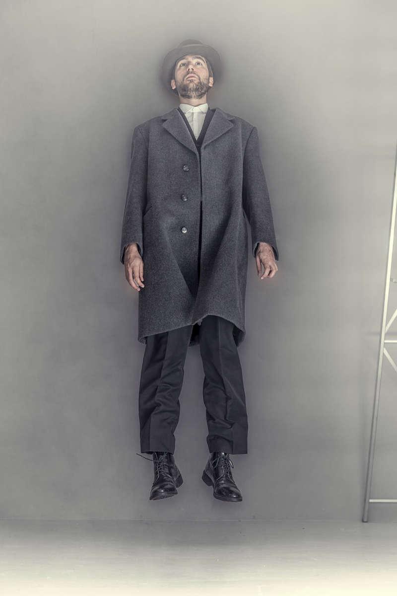 man levitating wearing vintage clothing
