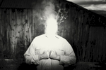 surreal photograph of a man with a bright lit smoking head