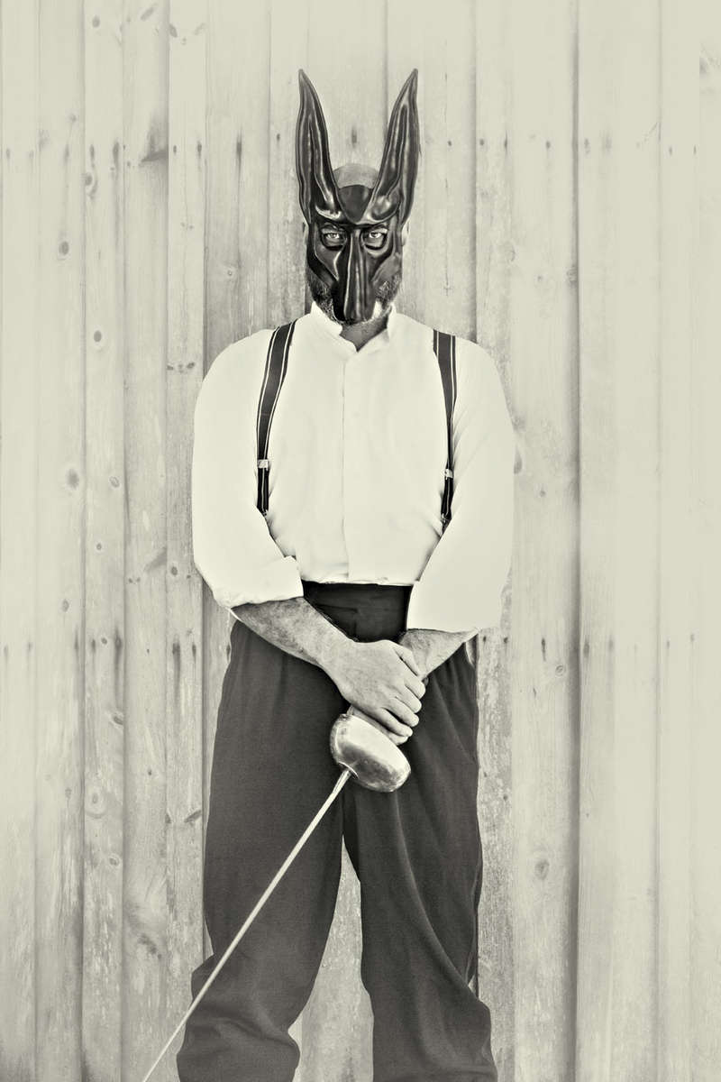 Man with a leather jackal mask and a sword