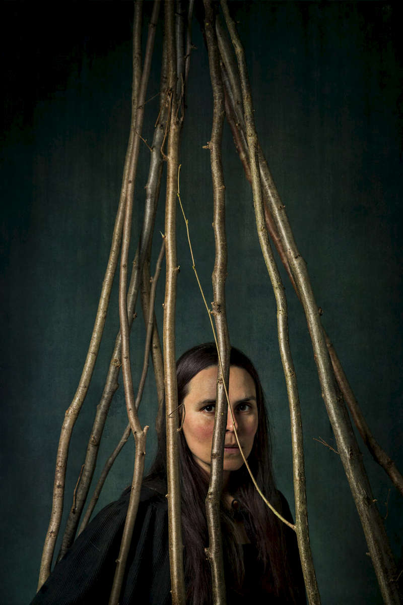 a portrait of a woman hemmed in by sticks