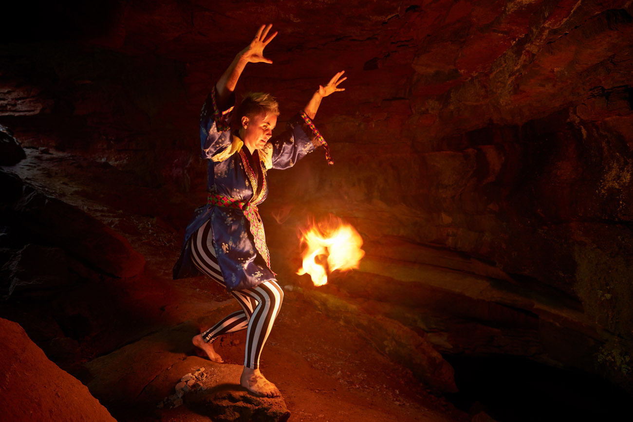 pagan woman in a dark cave with a ball of fire.