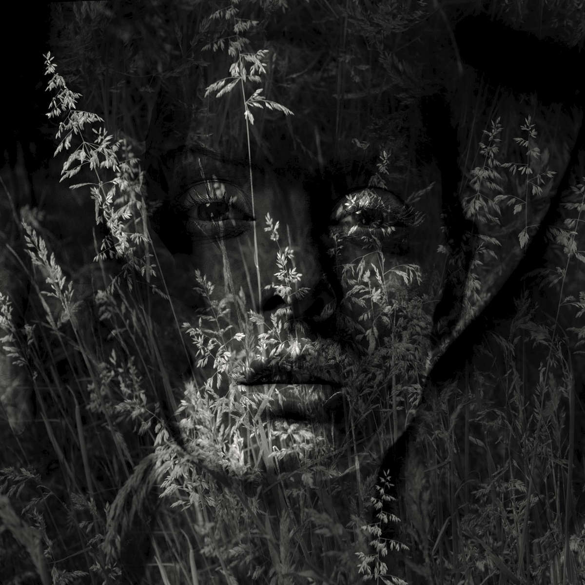 Double exposure nude portrait of a young woman with grasses