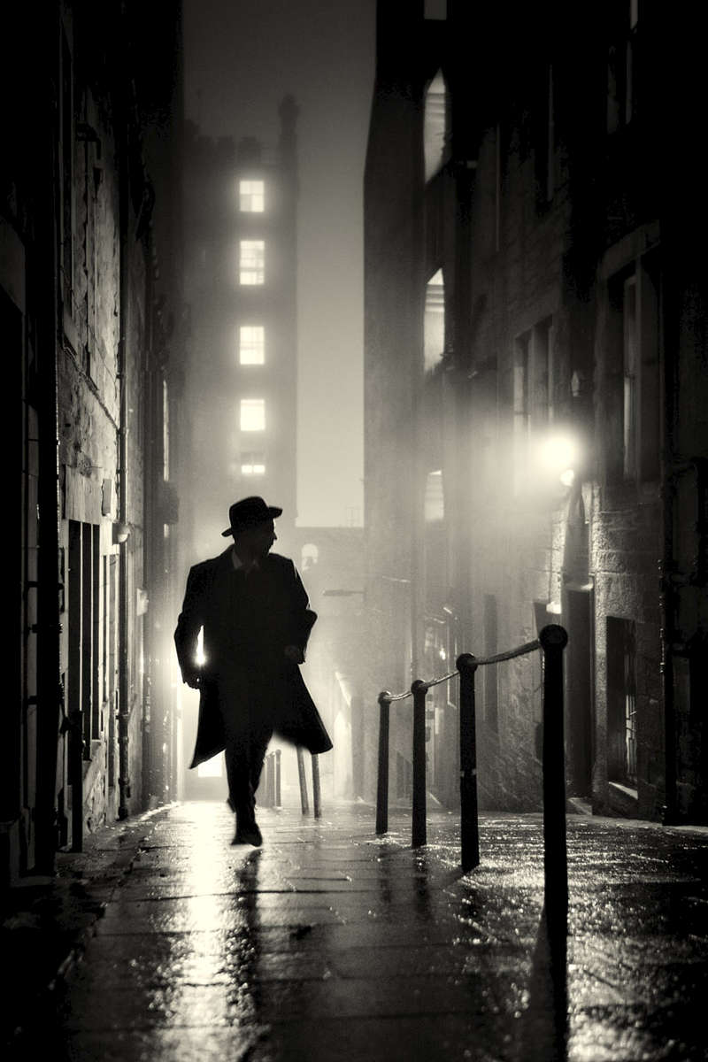 Dead of night noir portrait of a man in Edinburgh's old town close. Third man style