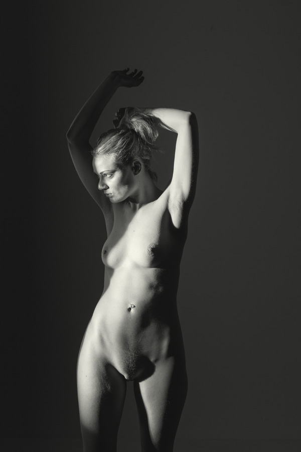 standing nude girl in a studio stretching her arms. Dark fine art beautiful girl
