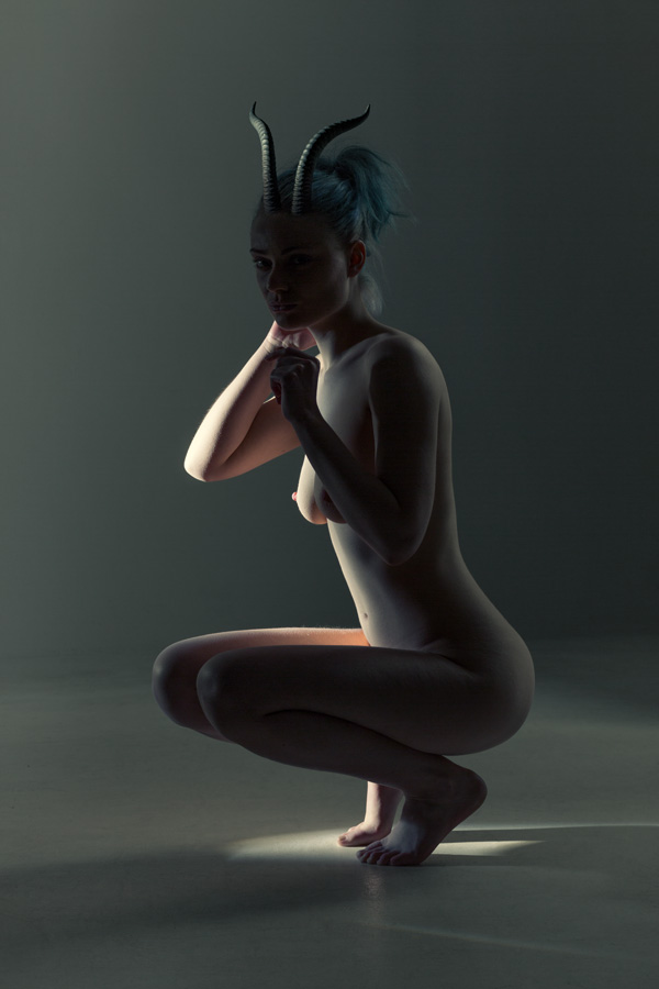 crouching naked woman in a dark lit studio wearing animal horns on her head.