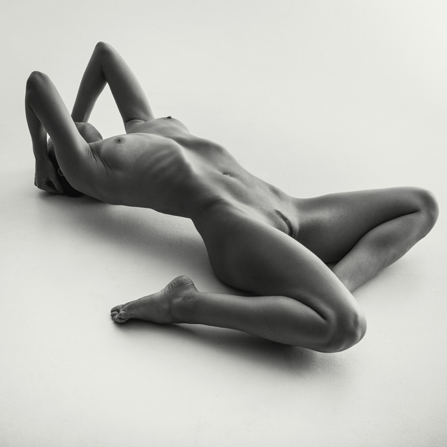naked woman lying on the floor on her back in an abstract pose