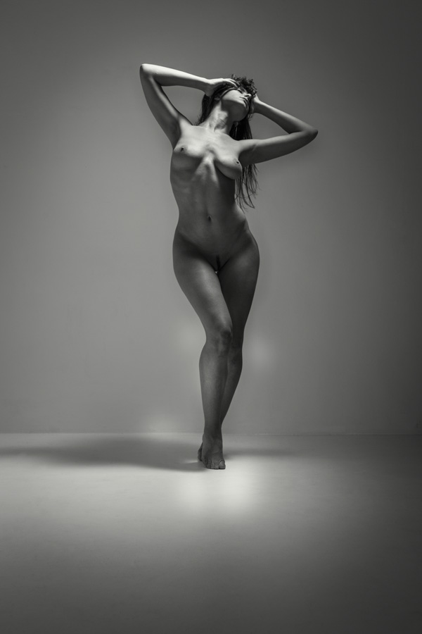 Nude photo of a beautiful shapely woman in a studio. Blkack and white fine art nude of a woman holding her head.