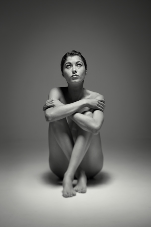 seated naked girl in a studio. Fine art b+w nude of a beautiful naked woman