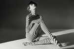 Nude of a beautiful seated woman with projected abstract stripes