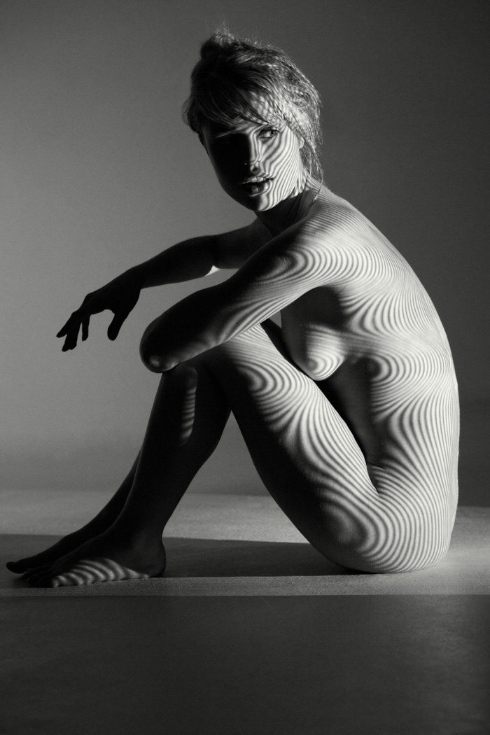 nude woman in studio with projector light casting stipes