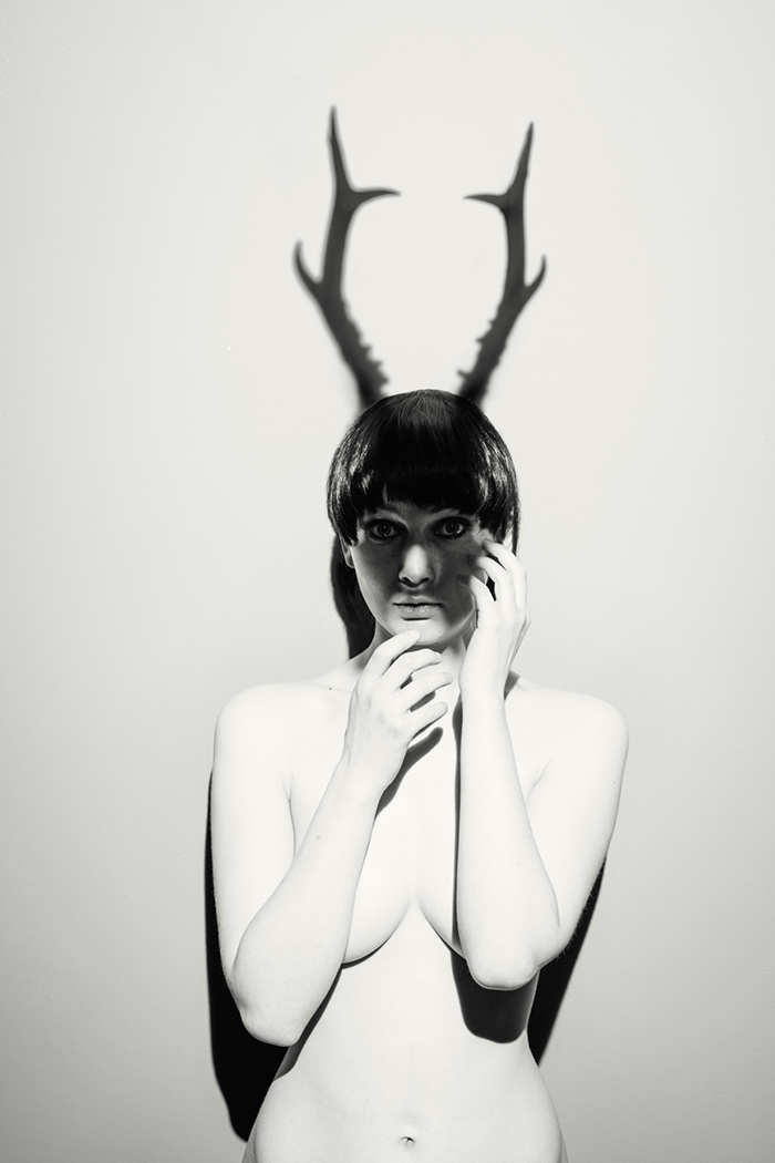 nude female model as mythical god cerynitis with the shadow of antlers