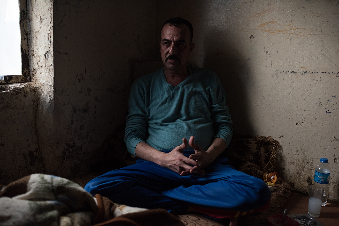 A Yazidi man living in the ruins of one of Saddam Hussein's palaces.  He fled with his family from the village of Dhola during the 2014 genocide perpetrated against the Yazidi by ISIS.  {quote}We have no future in Iraq.  Everything is broken for us{quote}.