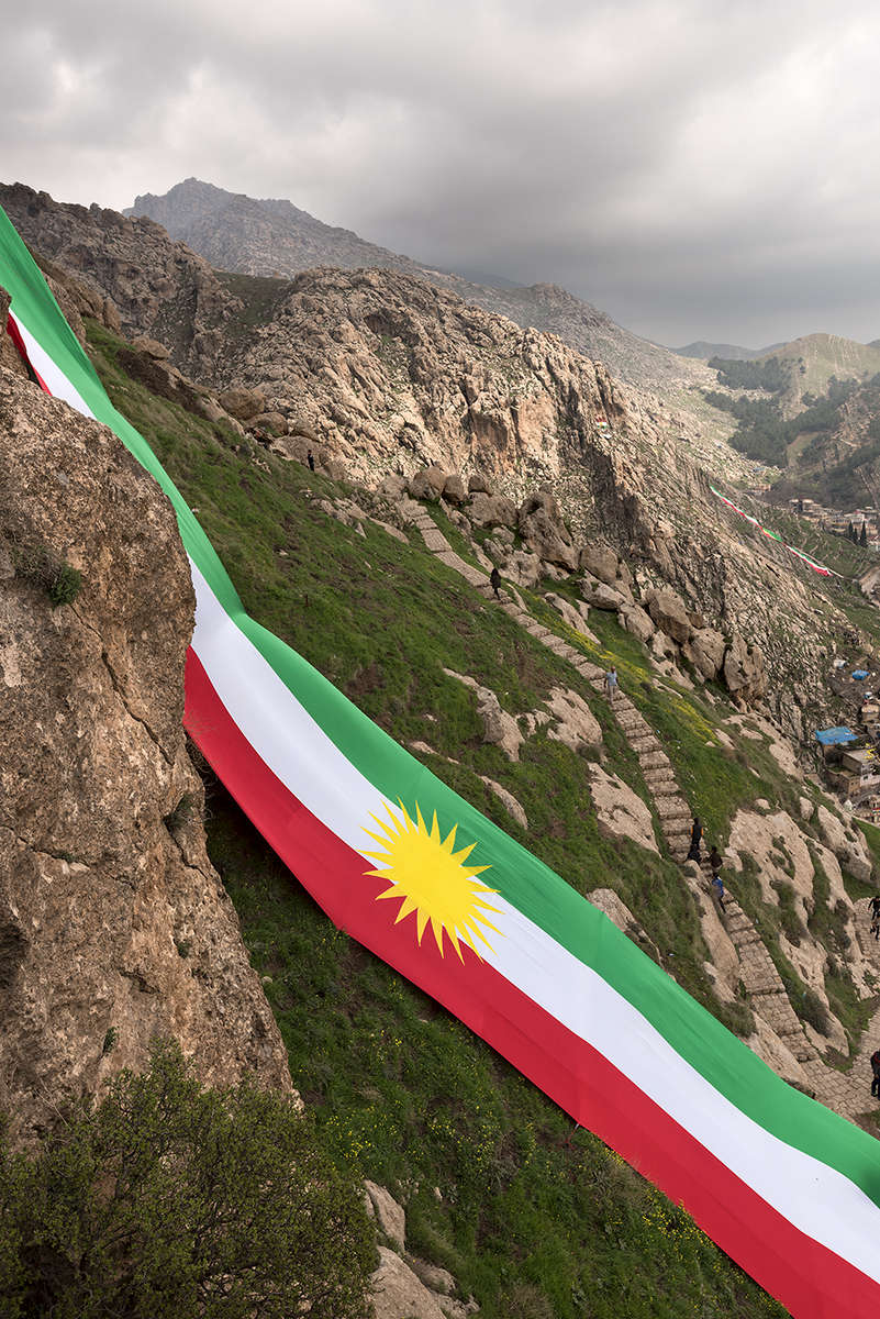 The Kurdish flag draped over the mountains of Akre.  On September 25th, 2017 the Kurdistan region of Iraq held a symbolic referendum.  They asked if they wanted to be a free people and their own nation.  It was a resounding yes.  This was immediately met with violence from Baghdad, Iran and Turkey.  There was no outside support for an independent nation for the Kurds.  This included the United States, whom after years of using the Peshmerga to fight ISIS, now {quote}remained neutral{quote} but whose weapons were used by the Iraqi military to kill Peshmerga soldiers along with Kurdish civilians.