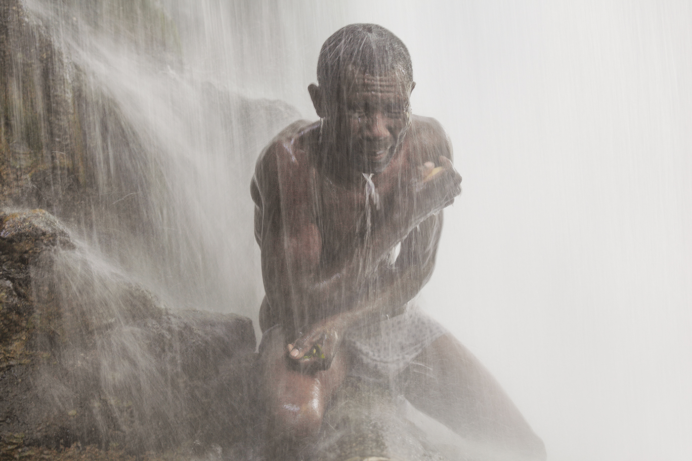 A pilgrim braces himself beneath the pounding waters of Saut-d'Eau.  The Vodou ancestor spirit, Danbhalah, is believed to have plunged into these abyssal waters in order to induce the abysses to give birth to the world.