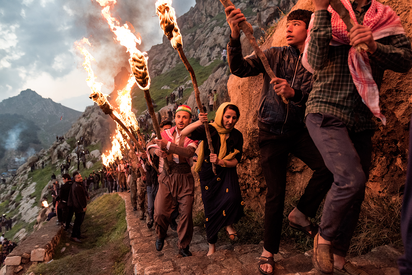 The ancient fire ceremony of Newroz marking the rite of Spring and the Kurdish New Year in the mountain city of Akre in northern Iraq.  A procession of torchbearers is led to the highest peak overlooking the city.  Fireworks and gunfire echo about in a celebration that has had special meaning since the fall of Saddam Hussein.  Previous to the American occupation in 2003, these people lived under the threat  of indiscriminate slaughter and genocide.  Now for the first time in centuries, they hold the beginnings of their own nation and the possibility of self-determination.  While still considered a province of Iraq, Kurdistan is the proud homeland of a people that have lived dangerously as outsiders for most of their history.