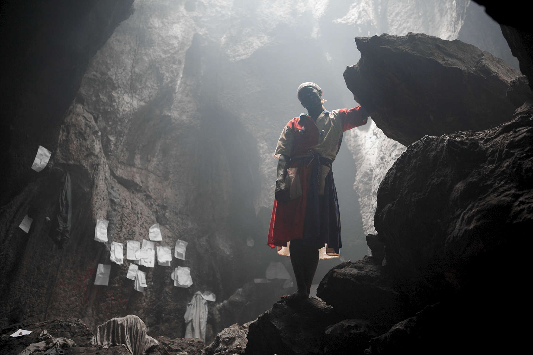 A Vodouisant pilgrim stands in smoky silhouette in the sacred grotto of St. Francis de Assisi.  White papers containing prayers and wishes are placed into the walls of this cave which was inhabited first by the native Taino indians and has since become a holy site of pilgrimage for the followers of Vodou.