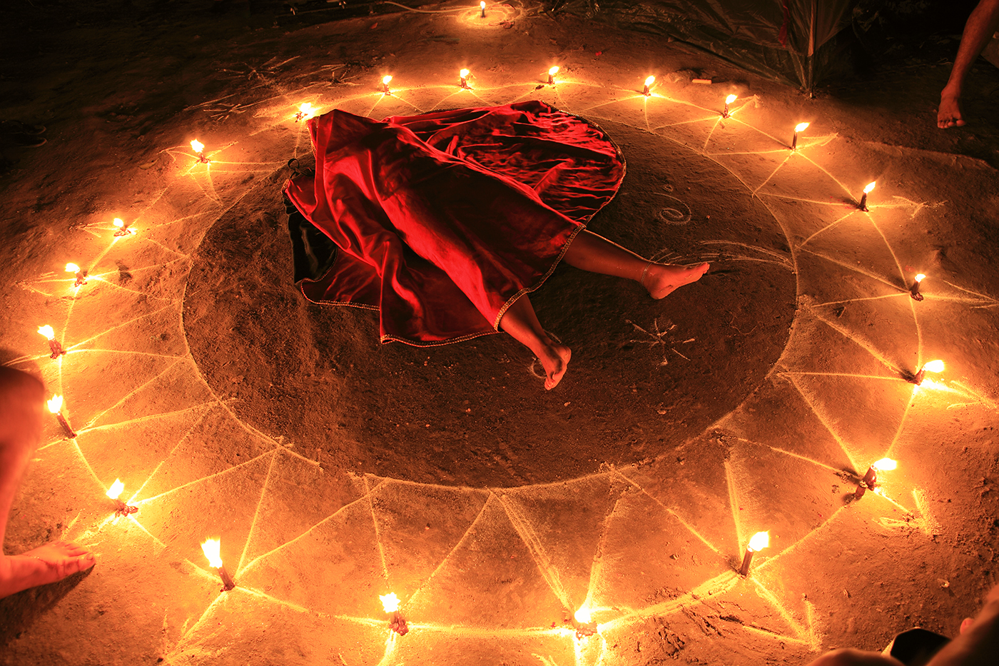 A night ritual begins.  The participant is placed inside the oracle to induce a trance-state and covered in a red shroud, symbolizing the nature of the spirit to be invoked.  The arrows point outward to the many directions the spirit must take on its difficult journey towards resurrection.
