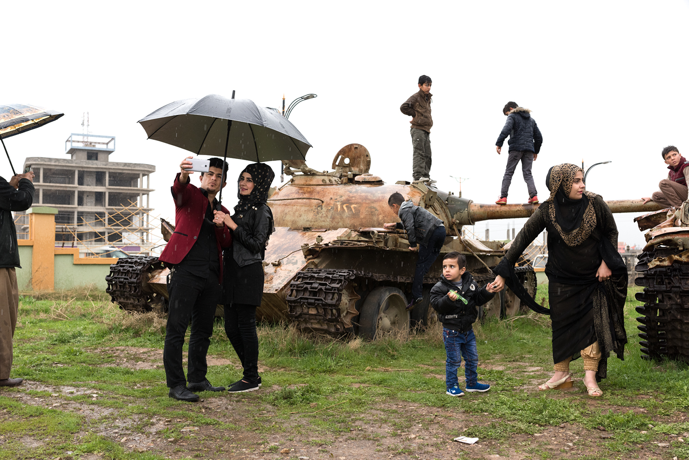 In Halabja, Kurdish families pose before tanks that were once used to exterminate them.  In 2006, the ex-president of Iraq, Saddam Hussein, was charged with the Anfal genocide which killed between 50,000 to 182,000 Kurds, and destroyed all ancestral Kurdish villages of north Iraq.