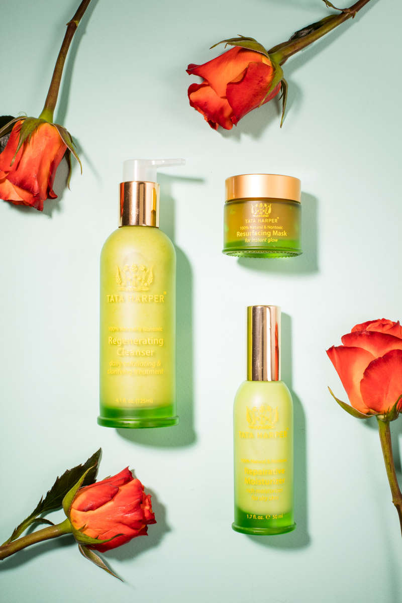 Tata Harper skincare and beauty product photography with roses on blue paper by Reciprocity Studio commercial photographers. Shot in Burlington, Vermont.