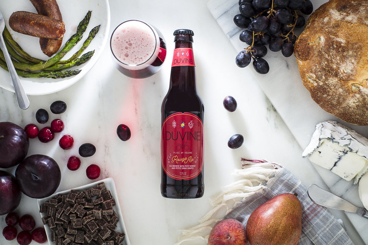 Magic Hat Brewing beer Duvine Rouge Ale on tabletop with a glass, pear, grapes, plums, chocolate, asparagus, cheeses and loaf of bread.