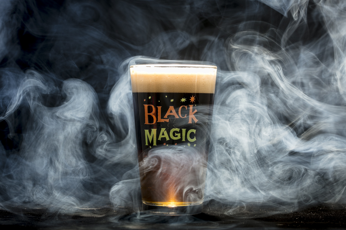 Magic Hat Brewing beer Black Magic pint glass against black fog background for Mardi Gras.
