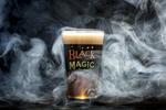 Magic Hat Brewing beer Black Magic pint glass against black fog background for Mardi Gras.