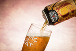 Magic Hat Brewing Company beer Number 9 Not Quite Pale Ale can being poured into a pint glass on pale pink background. By commercial photographers at JAM Creative.