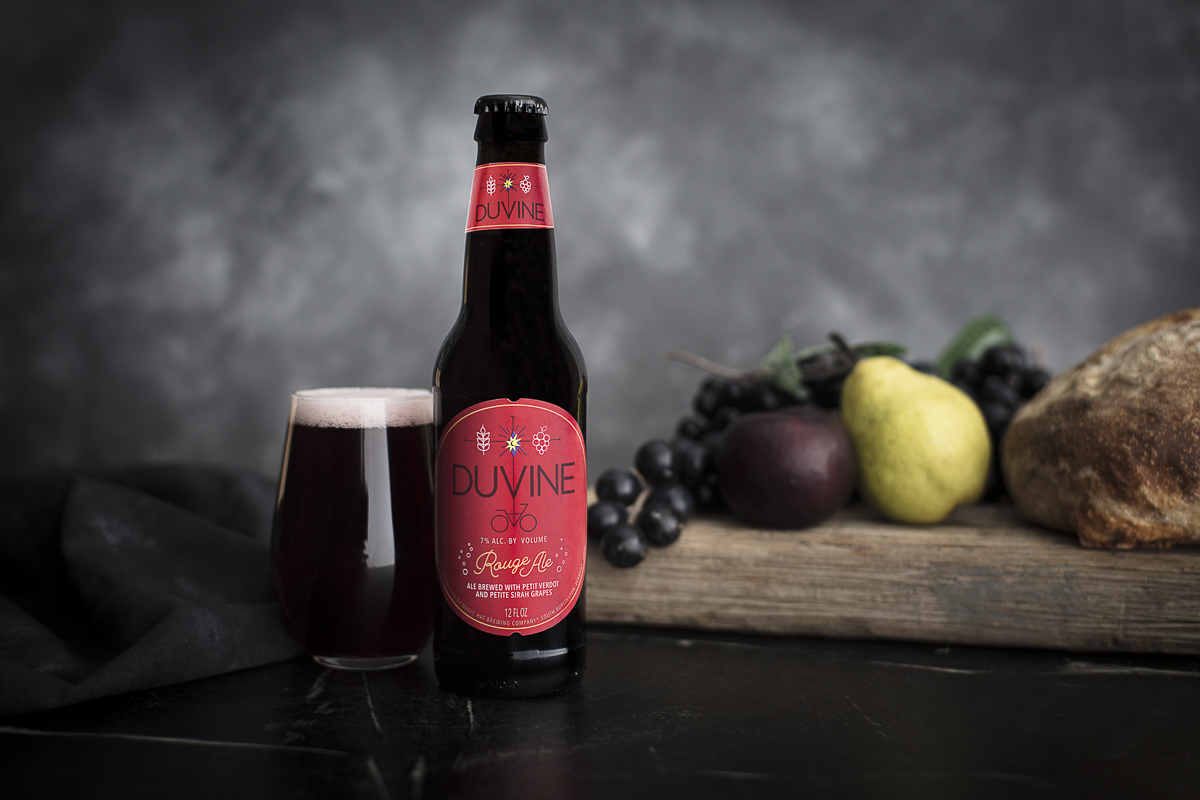 Magic Hat Brewing beer Duvine Rouge Ale on tabletop with a glass, pear, grapes and loaf of bread.