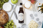 Magic Hat Brewing beer Duvine Blanc Ale on tabletop with a glass, pear, grapes and cheeses.