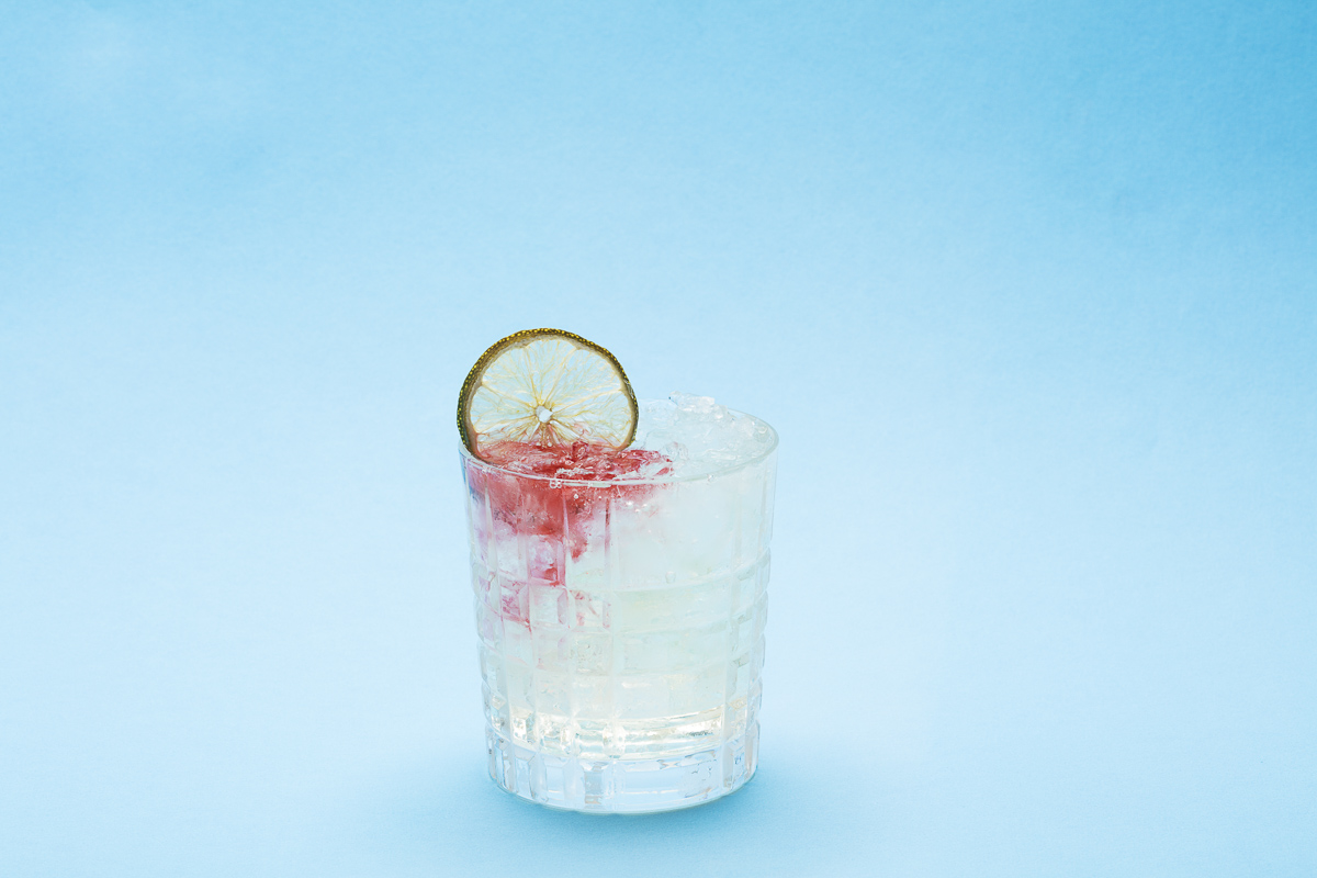 JAWS-themed Stonecutter Spirits cocktail with lime and blood in the water on a blue background. By commercial photographers at JAM Creative.