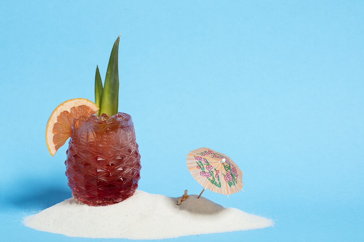 JAWS-themed Stonecutter Spirits tropical cocktail on sand and a blue background. By commercial photographers at JAM Creative.