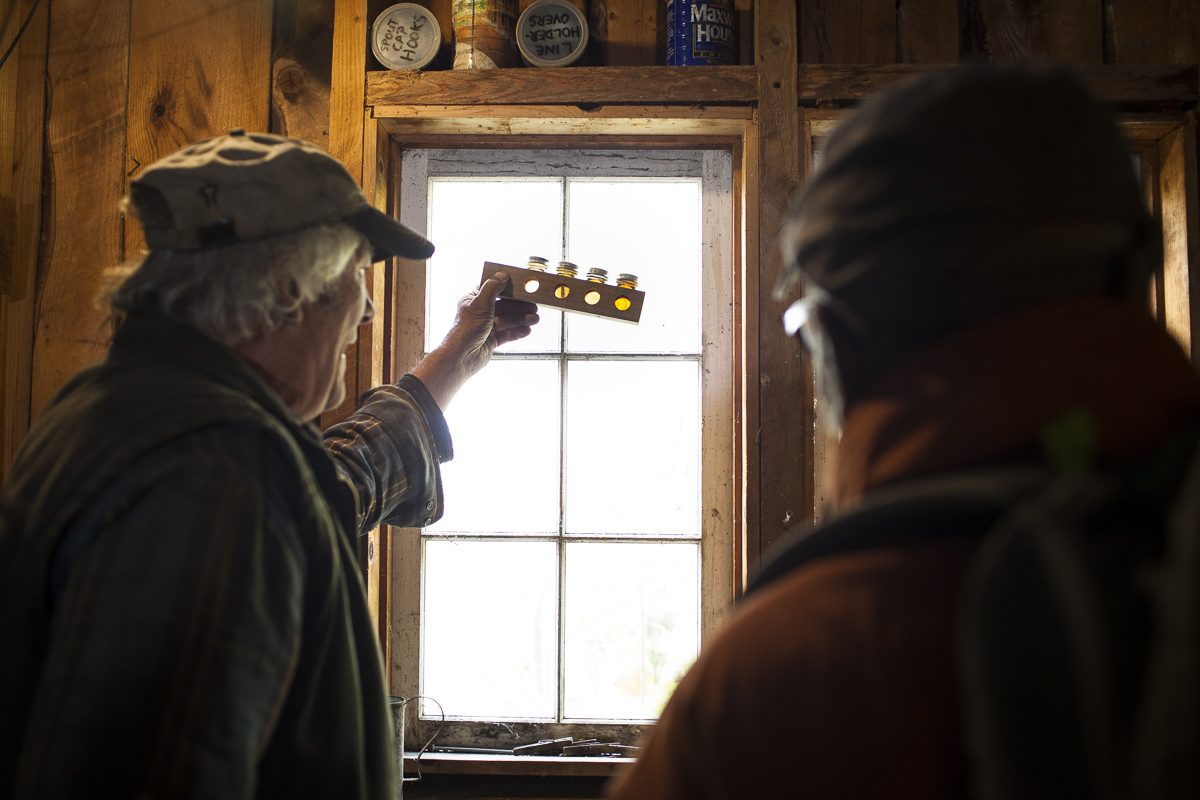 A patron on a Country Walkers guided tour examines the grades of maple syrup during their tour of a sugar house in Waterbury, Vermont. By JAM Creative.